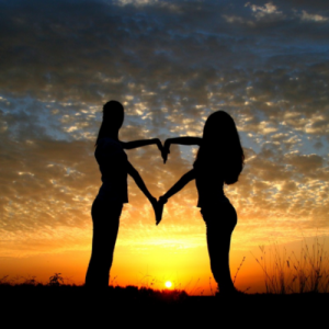two woman creating a heart shape with their arms