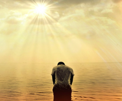 man in ocean with sunrays