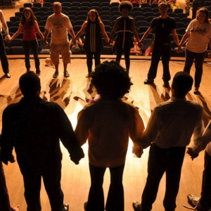 various people holding hands in a circle