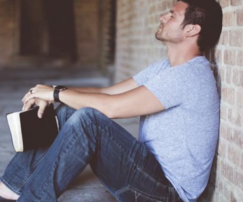homem pensando e segurando uma bíblia